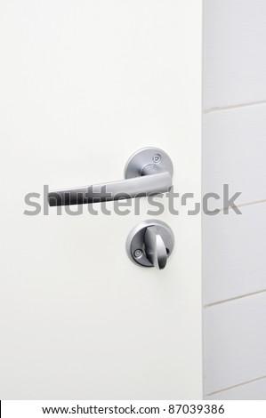Aluminum door knob on the white door