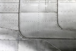 Aluminum fuselage and rivets on old airplane.
