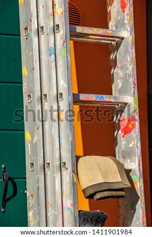 Aluminum ladder stained with colored paints for higher jobs for technicians, mechanics, artisans, engineers, artisans, etc. The concept of repair, art, paint
