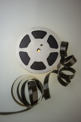 Aluminum reel with 16mm film on a colored background, close-up. Design element.