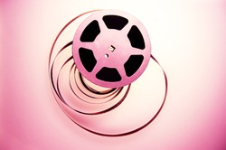 Aluminum reel with 16mm film strip on a colored background. Design element.