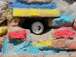 Aluminum soda can hidden in a hole a colorful brick wall
