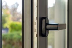 Aluminum window detail. Metal door frame open closeup view. Energy efficient, safety profile, blur green outdoor background