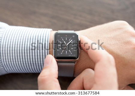 Alushta, Russia - September 1, 2015: Man hand with Apple Watch on the desk. Apple Watch was created and developed by the Apple inc.