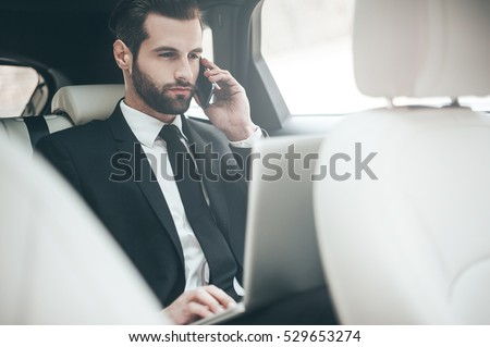 Always available. Handsome young businessman working on his laptop and talking on the phone while sitting in the car