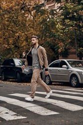 Always careful. Full length of handsome young man in casual wear walking across a zebra crossing while spending time outdoors