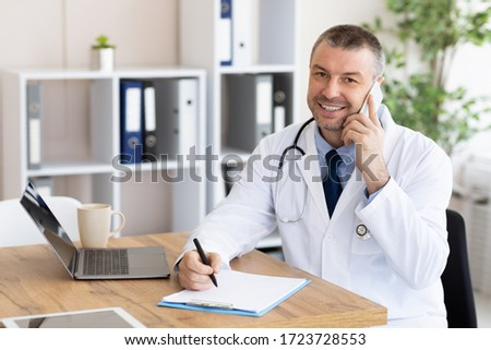 Always Ready To Help. Happy doctor talking on phone with his patients and writing notes, working at his office Stockfoto ©
