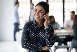 Always welcome! Cheerful positive young indian lady manager agent consultant standing at workplace in office holding phone at her ear talking to client making answering call counseling giving advice