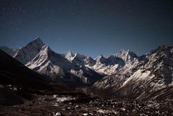 Ama Dablam mountain panoramic view on a starry night. Beautiful night mountain landscape under bright moonlight. Stars above himalayan mountain range, Everest Base Camp Trek, Himalayas, Nepal.