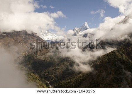 Ama Dablam to the right and in the middle Nuptse, Lhotse, and Everest emerge from the clouds.