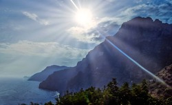 Amalfi coast scenic dreamy landscape view of rocky mountains Lattari range silhouette in fog at Tyrrhenian sea on sunny Summer day with shining Sun rays on blue sky, soft focus photo, Italy. Campania.