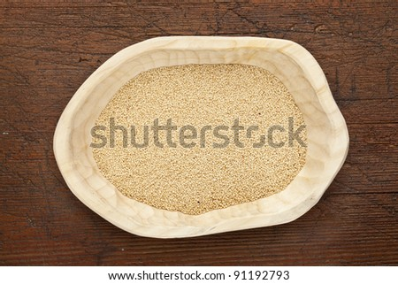 amaranth in a rustic wood bowl against grunge dark wooden table surface, top view