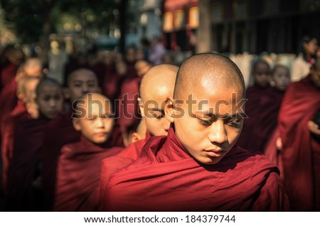 AMARAPURA, MYANMAR - FEBRUARY 10, 2014: young buddhist novices walk to collect alms and offerings in the monastery of Maha Gandhayon Kyaung near Mandalay in Myanmar.