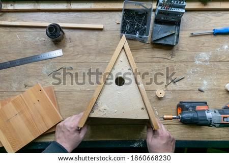 Amateur carpenter with wooden birdhouse. Stockfoto ©