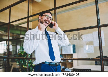 Amazed and excited entrepreneur with  winning Yes gesture celebrating successful news received by telephone conversation. Happy man office worker emotionally conversing via cellular feeling success #793480405