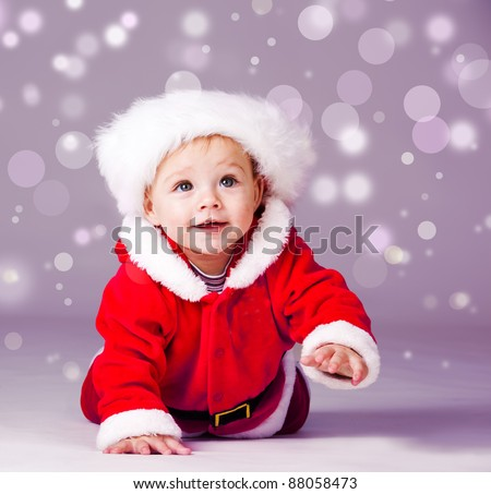 Amazed attractive baby boy in Christmas  costume crawling