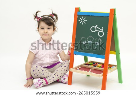 Amazed baby girl draw flowers, a bike and Sun on black board with chalk isolated on white