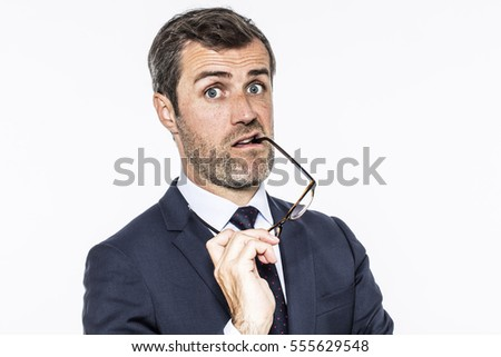 amazed bearded middle aged businessman biting his eyeglasses for corporate interrogation or suspicion, copy space, white background studio
