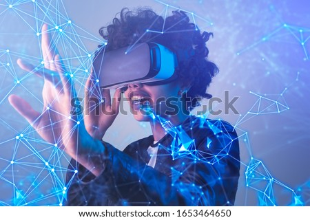 Amazed black female in modern VR glasses interacting with network while having virtual reality experience