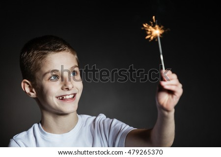 Amazed brown haired boy with blue eyes in white shirt holding lit sparkler #479265370