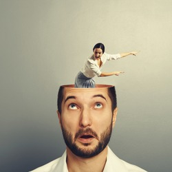 amazed businessman with open head. young screaming businesswoman standing into the head, looking at the man and showing the direction. photo over grey background