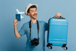 Amazed caucasian guy in a hat with photocamera, holds a blue suitcase and a small airplane with passport, looks at the camera, smiles, happy about of a long-awaited vacation, isolated blue background