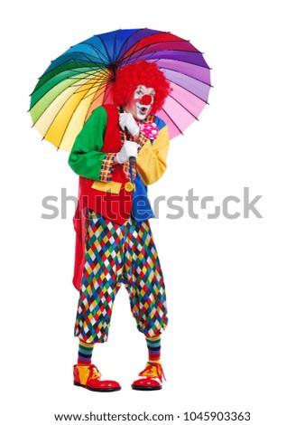 Amazed clown under rainbow umbrella full length picture against white background