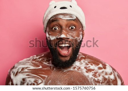 Amazed emotional dark skinned man has refreshing shower, foam on body, uses cosmetic for men, enjoys daily routine in douche, opens mouth from excitement, stands naked over pink wall, washes