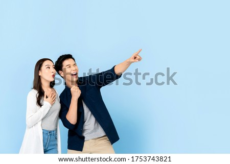 Amazed excited Asian couple tourists pointing hand to empty space on isolated light blue background