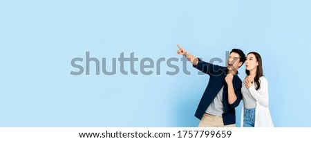 Amazed excited Asian couple tourists pointing hand to empty space on isolated light blue banner background