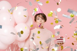 Amazed fun young woman in casual sweater hat celebrating with falling confetti hold air balloons cake blowing in pipe isolated on pastel pink background. Birthday holiday party people emotions concept