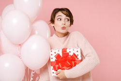 Amazed fun young woman in knitted casual sweater looking aside hold bunch of air balloons, red present box with gift ribbon bow celebrating birthday holiday party isolated on pastel pink background.