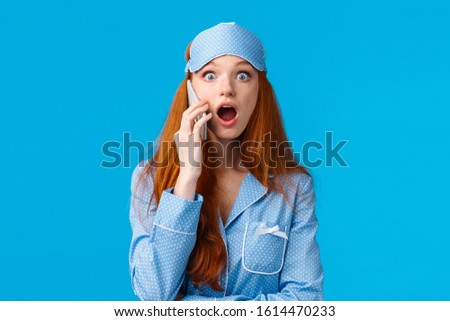 Amazed girl found out shocking news as talking friend on phone. Shocked and astonished startled young redhead woman in sleep mask and pyjama stare impressed, holding smartphone, blue background
