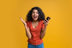 Amazed girl with mobile phone in hands celebrating victory in online casino, hitting jackpot in lotttery, making bets online at bookmaker's website. Female blogger happy to get one million followers.