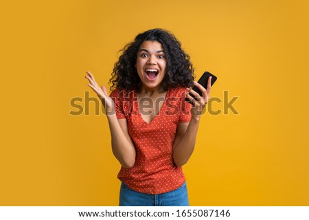 Amazed girl with mobile phone in hands celebrating victory in online casino, hitting jackpot in lotttery, making bets online at bookmaker's website. Female blogger happy to get one million followers.  Foto stock ©