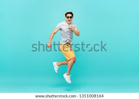 Amazed handsome Asian tourist man jumping studio shot isolated on light blue background