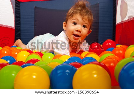 Amazed happy baby laying on colorful balls in playpan