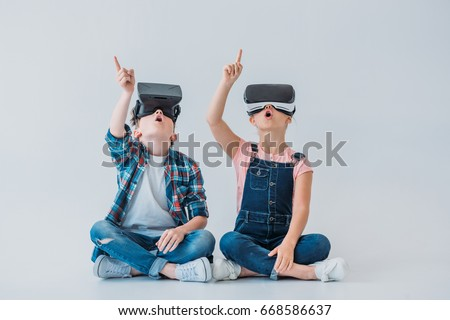 amazed kids using virtual reality headsets and pointing up with finger while sitting on the floor