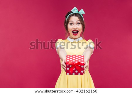 Amazed lovely young woman holding and giving present box to you over pink background #432162160