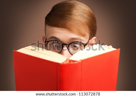 amazed nerd reading a red book with eyeglasses