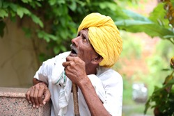 Amazed old Indian man wearing yellow turban looking up with mouth opened. Curious old man. Wearing traditional Indian clothes. Old man holding stick in hand. Old man waiting for his turn.