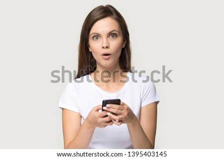 Amazed pretty woman in white t-shirt holds smart phone looks at camera pose isolated on grey studio background, shocking news or great notice about new application free download, better offer concept #1395403145