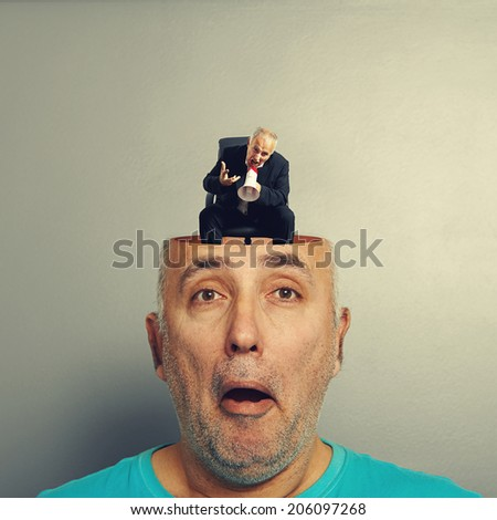 amazed senior man with open head. angry small businessman screaming with megaphone in the man\'s head. photo over grey background