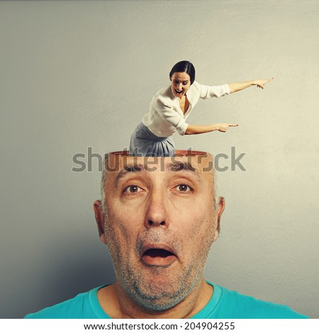 amazed senior man with open head. young screaming businesswoman standing in the head, looking at the man and pointing at something. photo over grey background