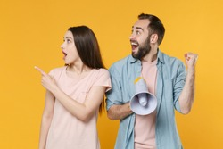 Amazed shocked couple two friends man woman in casual clothes scream in megaphone pointing index finger aside on mock up workspace, doing winner gesture isolated on yellow background studio portrait.