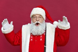 Amazed shocked funny old bearded Santa Claus face wearing costume looking at camera with open mouth, surprised advertising Christmas promotion, New Year xmas discount ad isolated on red background.