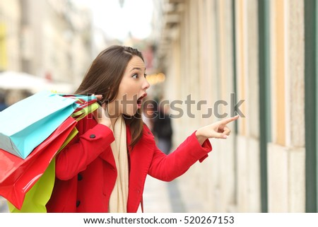 Shutterstock Amazed shopper opening mouth holding shopping bags watching special offers in stores and pointing in the street in winter
