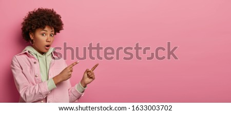 Amazed stunned dark skinned woman points index fingers on copy space area, looks with puzzlement and confusion, opens mouth, dressed in casual jacket, isolated on pink studio wall. Omg, look there