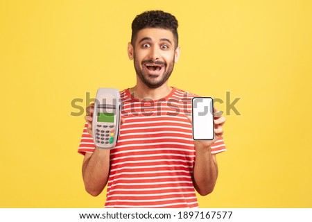 Amazed surprised bearded man in striped t-shirt showing contactless payment terminal and empty display smartphone, looking at camera with astonishment. Indoor studio shot isolated on yellow background Photo stock ©