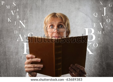 Amazed woman reading a book with letters flying away from it